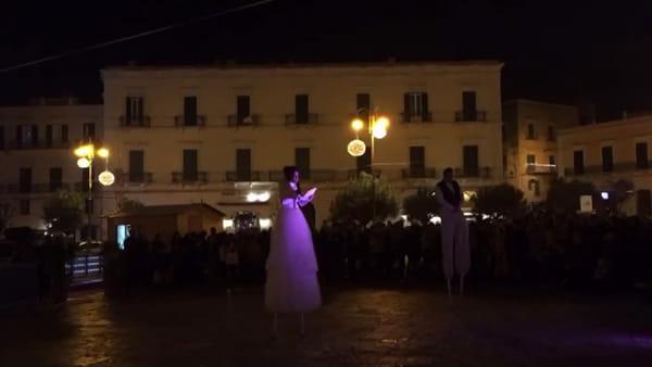 Gli artisti danzano in piazza sui trampoli: la proposta di matrimonio incanta i presenti
